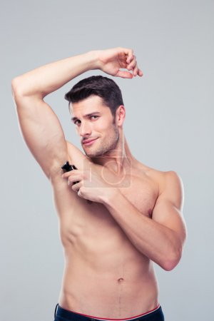 Handsome man shaving his armpit