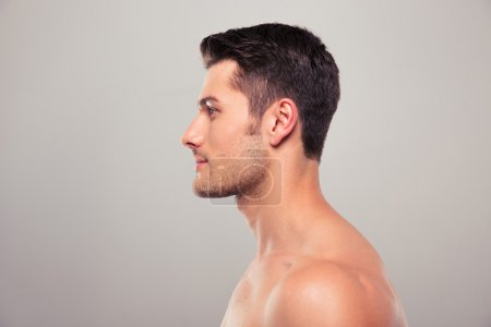 Side view portrait of a young man with nude torso