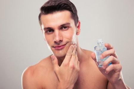 Man applying lotion after shave on face