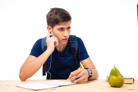 Male student sitting on exam with headphones