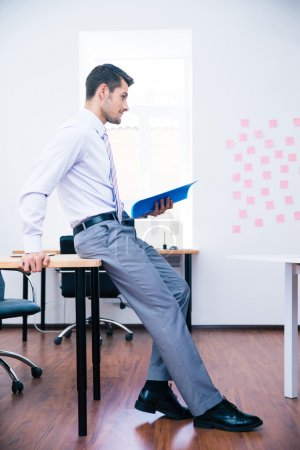Pensive businessman leaning on the table with folder