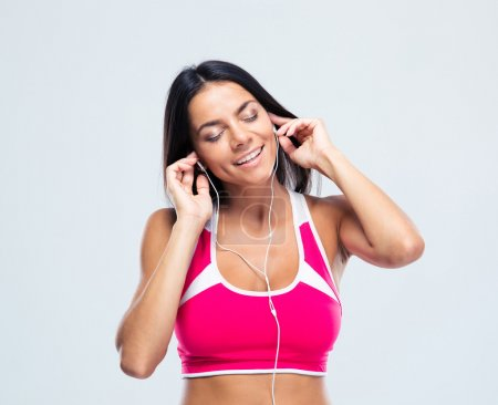 Cheerful woman listening music in headphones
