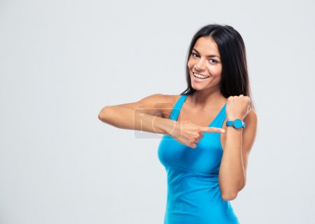 Photo for Happy fitness woman pointing on fitness tracker over gray background - Royalty Free Image