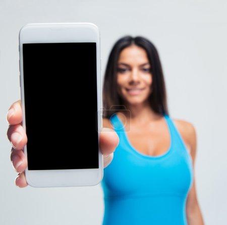 Happy woman showing blank smartphone screen