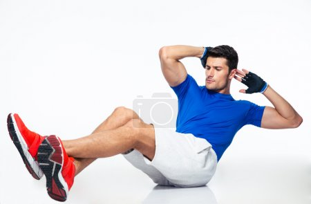 Photo for Sports man doing abdominal exercises isolated on a white background - Royalty Free Image
