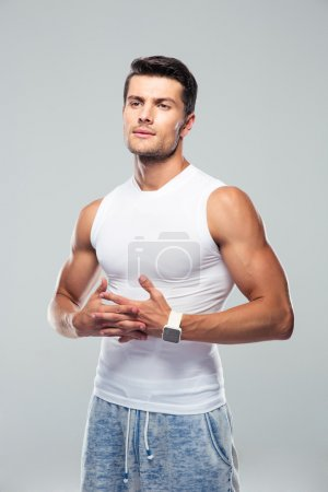 Fitness man standing over gray background