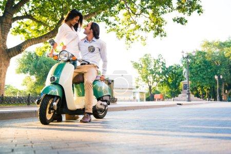 Happy beautiful couple flirting on scooter