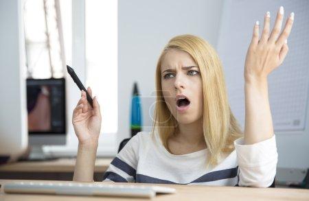 Photo pour Jeune femme fâché travaillant sur l'ordinateur dans le bureau - image libre de droit