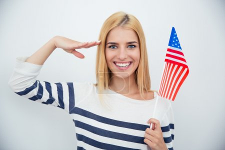 Photo pour Happy patriotic woman holding USA flag over gray background - image libre de droit