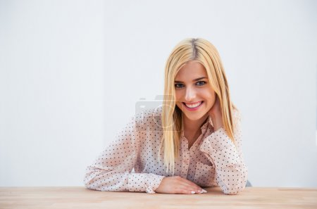 Happy young businesswoman sitting at the table