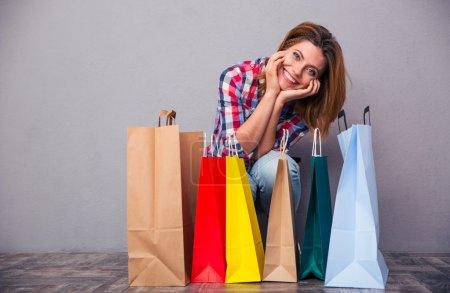 Foto de Retrato de una mujer casual sonriente sentada con bolsas de compras en el estudio. Mirando la cámara - Imagen libre de derechos