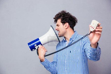 Man directing megaphone at herself