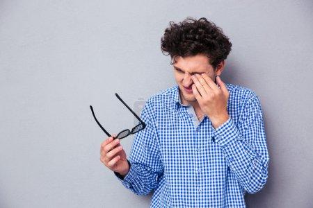 Photo pour Homme tenant des lunettes de soleil et frottant ses yeux sur fond gris - image libre de droit