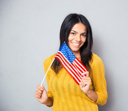 Photo for Smiling young woman holding american flag over gray background and looking at camera - Royalty Free Image