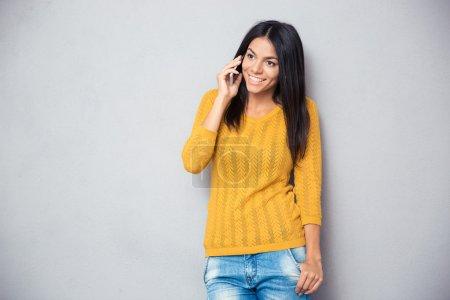 Photo pour Heureuse jeune femme parlant au téléphone sur fond gris - image libre de droit