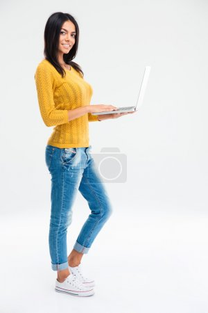 Happy woman standing with laptop