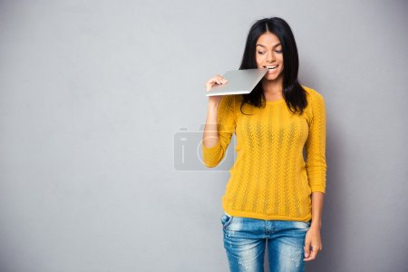 Casual woman biting tablet computer