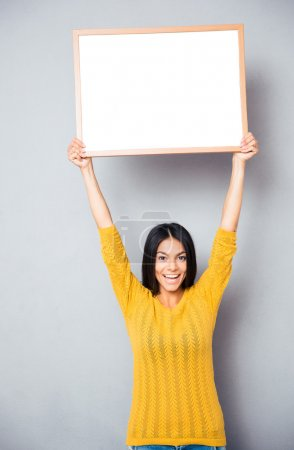 Smiling woman holding blank board