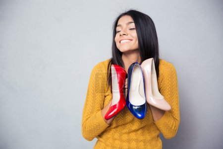 Happy woman holding shoes