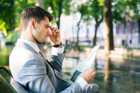 Photo for Thoughtful businessman reading newspaper outdoors - Royalty Free Image