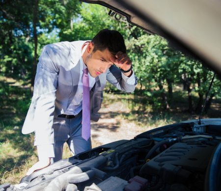 Photo for Businessman looking under the hood of breakdown car in forest - Royalty Free Image