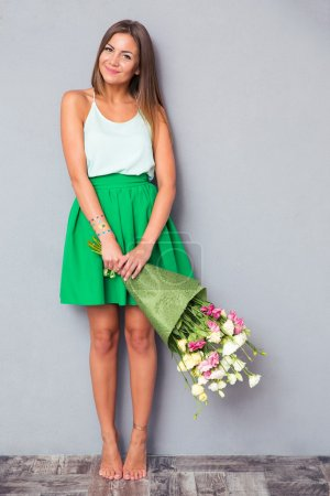 Photo for Full length portrait of a smiling cute girl holding bouquet with flowers on gray background - Royalty Free Image