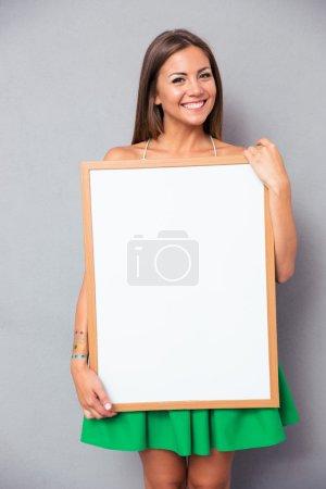 Photo pour Souriante jeune femme tenant Conseil blanc sur fond gris - image libre de droit