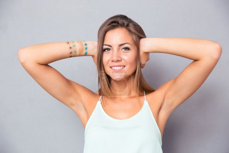 Smiling woman covering her ears