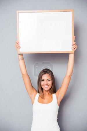 Photo pour Souriant jeune fille tenant tableau blanc sur fond gris. Regardant la caméra - image libre de droit