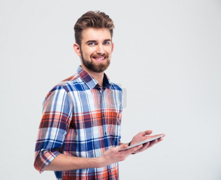 Photo for Portrait of a smiling man holding tablet computer and looking at camera isolated on a white background - Royalty Free Image