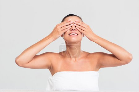 Smiling woman in towel covering eyes with hands