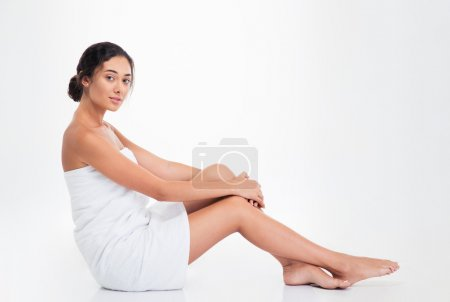 Beautiful young woman in towel sitting on the floor