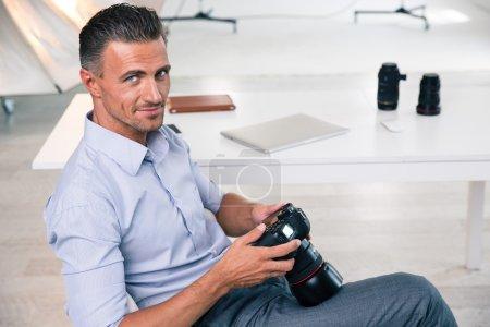 Smiling handsome photographer using camera
