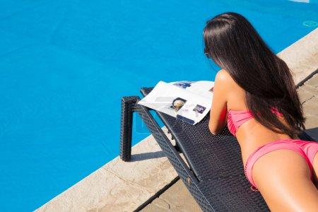 Girl lying on deckchair and reading magazine