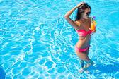 Žena pít koktejl v bazénu