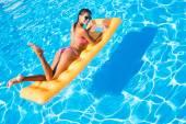 Žena leží na nafukovací matrace v bazénu