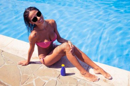 Happy woman sunbathing near swim pool