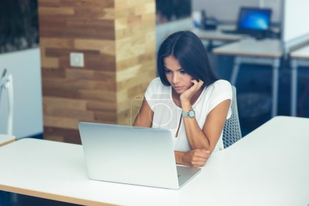 Photo for Portrait of a beautiful woman working on laptop in office - Royalty Free Image