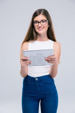 Photo for Portrait of a smiling female teenager in glasses holding tablet computer and looking at camera isolated on a white background - Royalty Free Image
