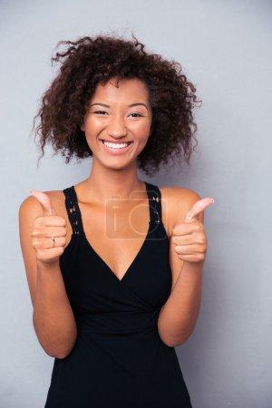 Photo pour Portrait d'une femme africaine souriante montrant pouce vers le haut sur fond gris - image libre de droit