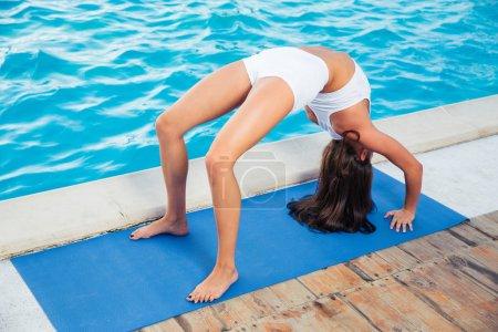Woman doing yoga bridge pose outdoors