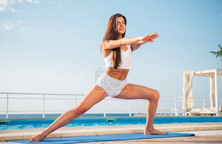 Portrait of a young woman doing stretching exercis...