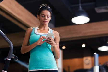 Woman using smartphone in fitness gym