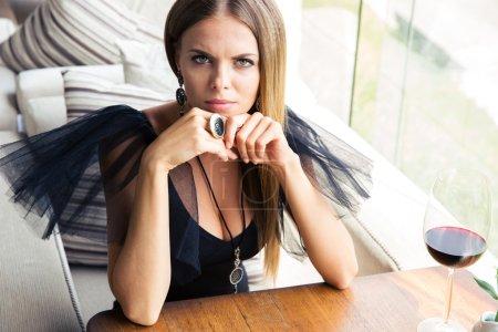 Woman sitting in fashion dress at restaurant