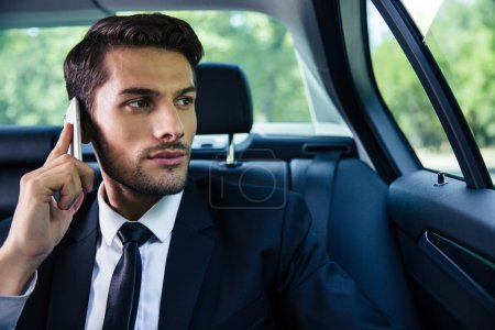 Businessman talking on the phone in car