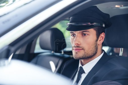 Photo for Portrait of a handsome male chauffeur sitting in a car - Royalty Free Image