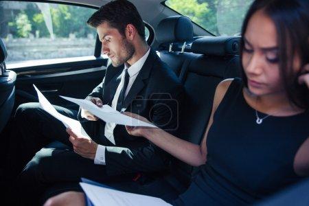 Photo pour Femme d'affaires et homme d'affaires, lecture de documents sur le siège arrière de voiture - image libre de droit
