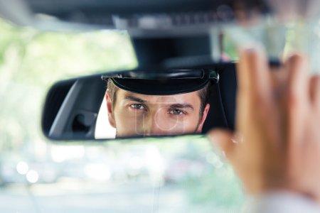 Photo pour Homme chauffeur assis dans une voiture et regardant son reflet dans un miroir - image libre de droit