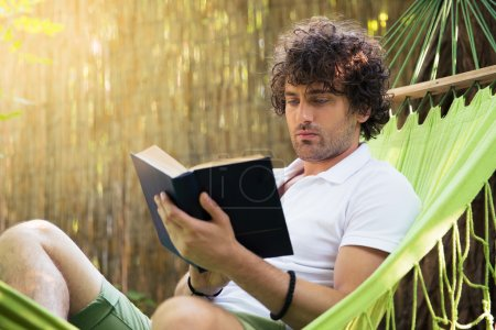 Man reading book outdoors