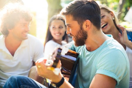 Friends with guitar having fun outdoor